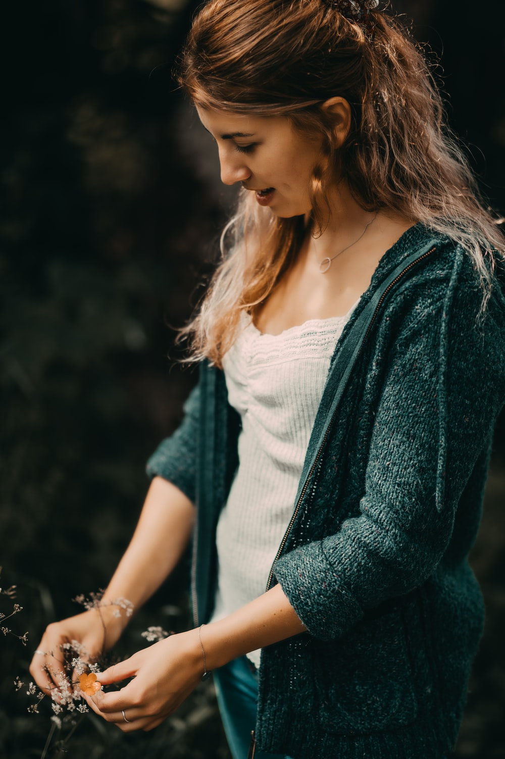 woman in white tank top and green cardigan