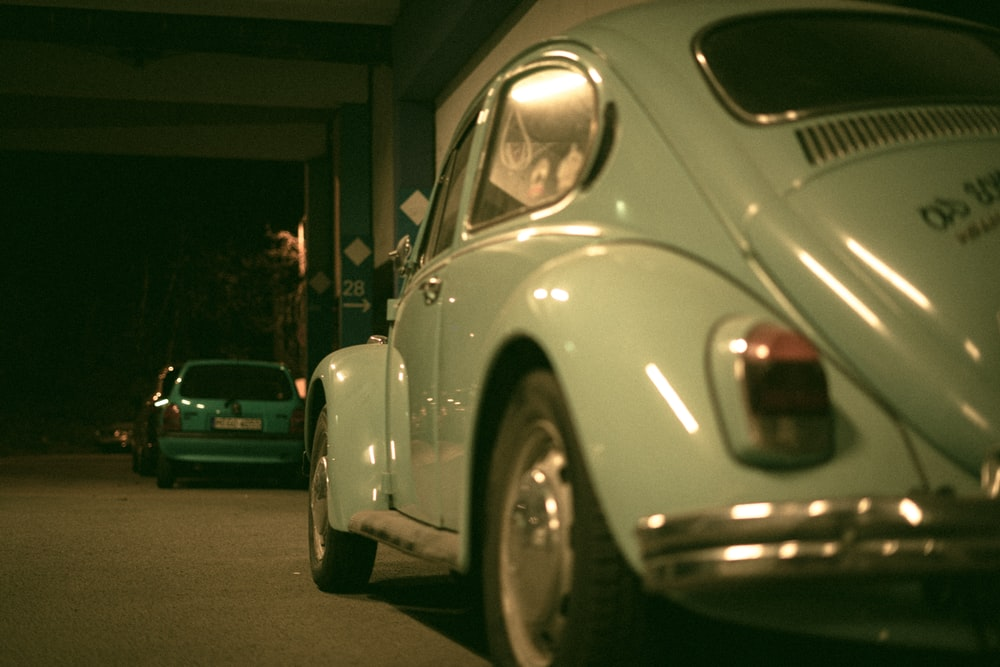 white volkswagen beetle parked on side of the road during night time