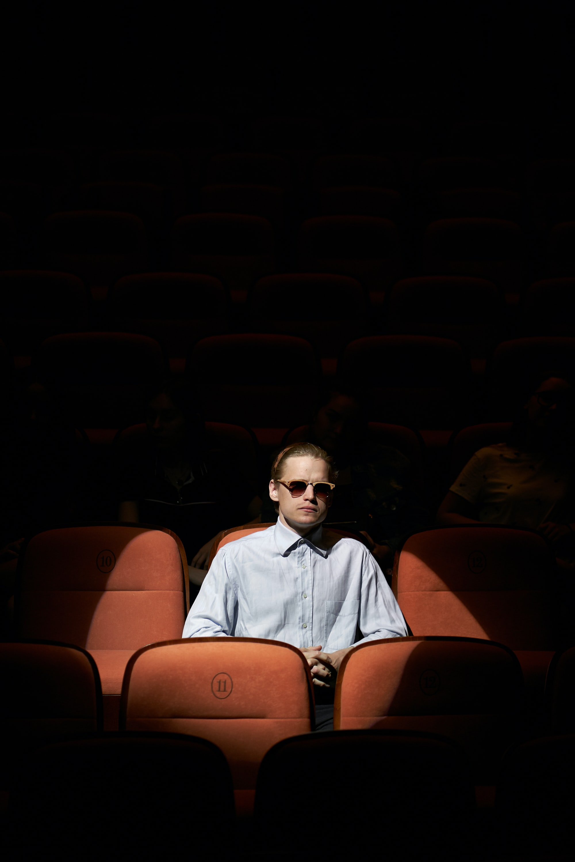 A lone man sitting under the spotlight in the theatre hall.
