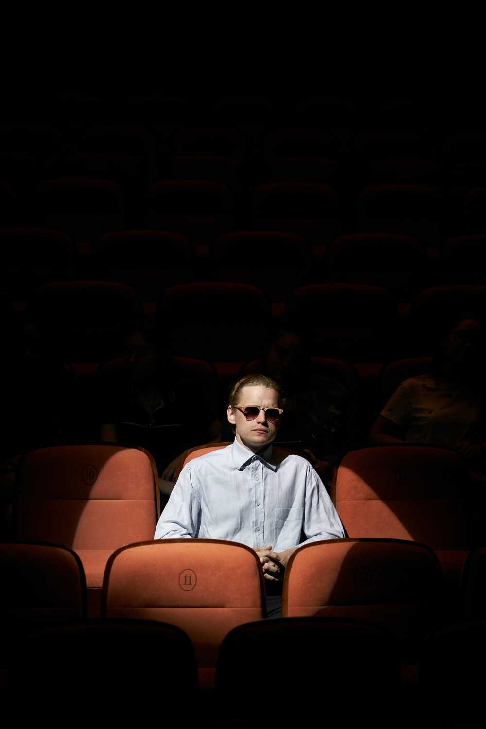 man in blue dress shirt wearing sunglasses sitting on brown chair