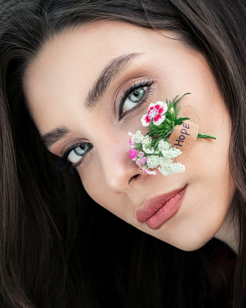 woman with green flower on her face