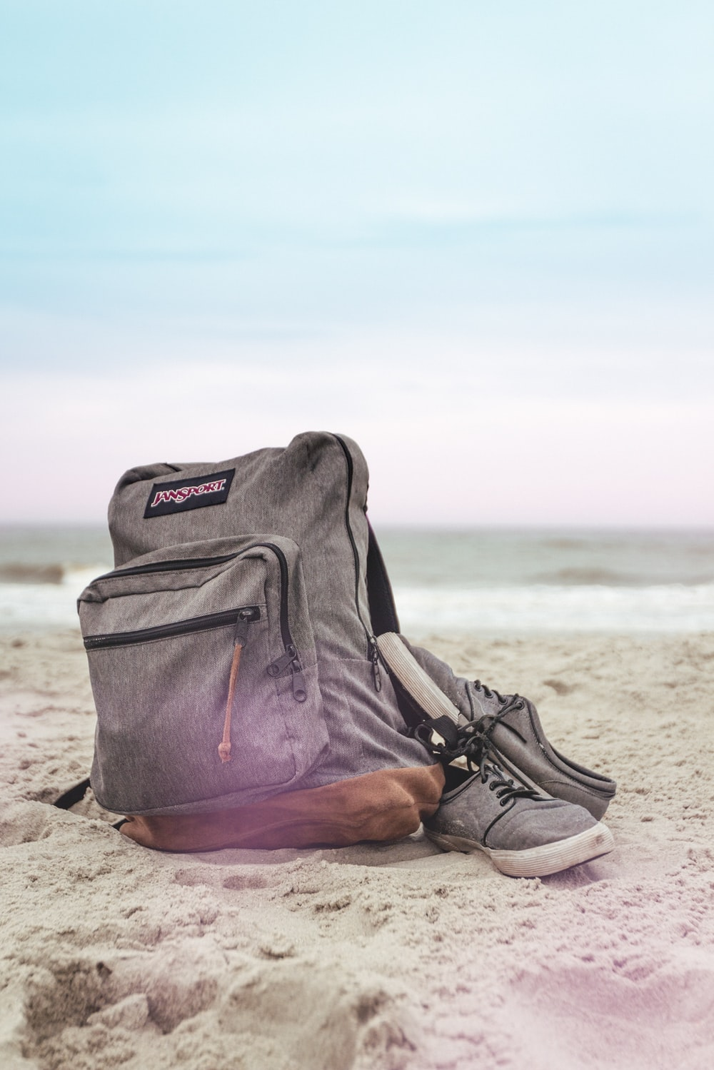 black and red nike backpack on brown sand near body of water during daytime