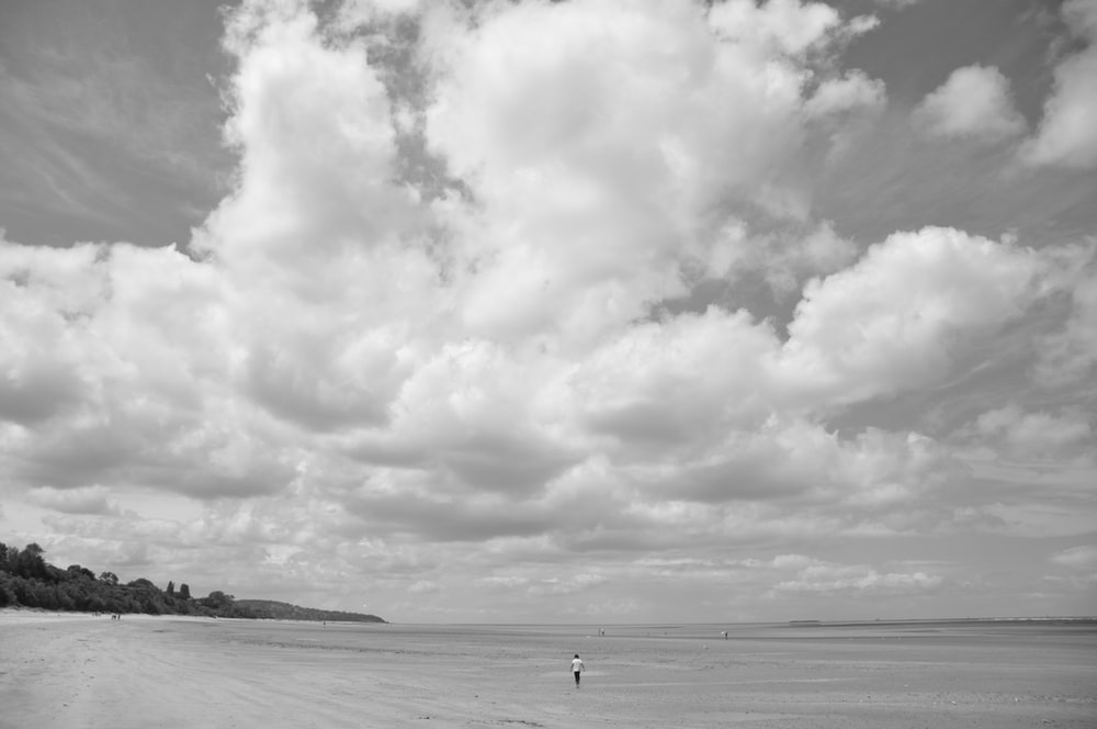 grayscale photo of person walking on beach under cloudy sky
