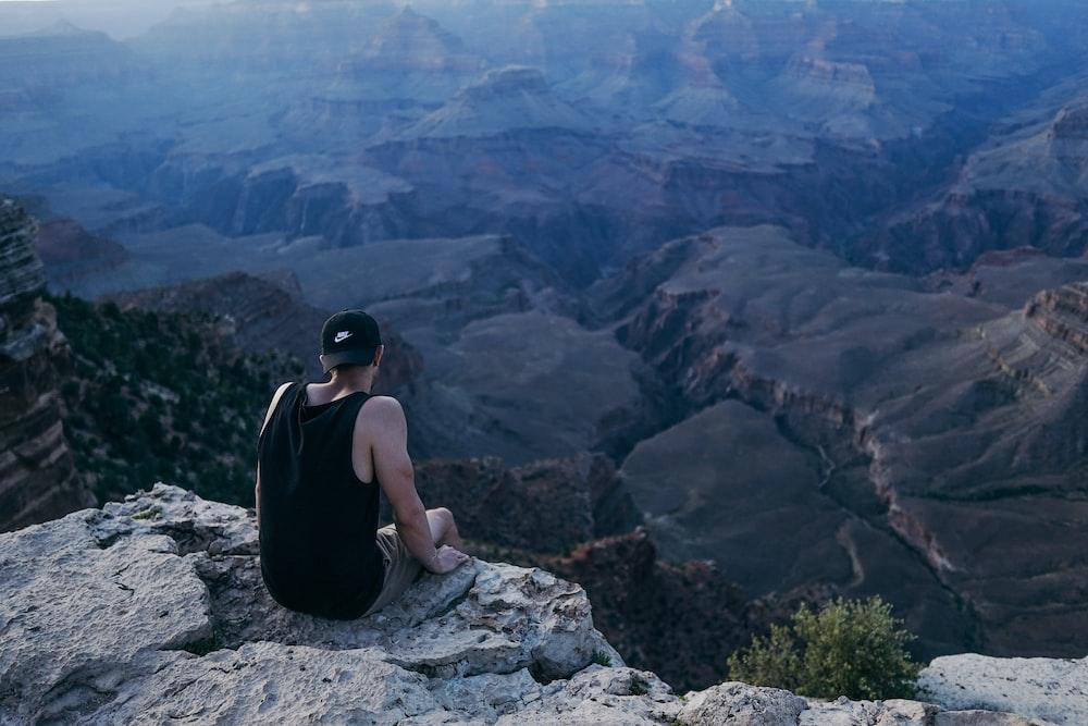 man in black tank top sitting on rock during daytime
