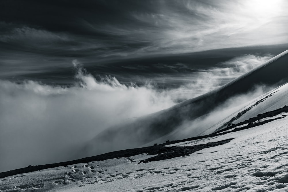 grayscale photo of snow covered mountain under cloudy sky