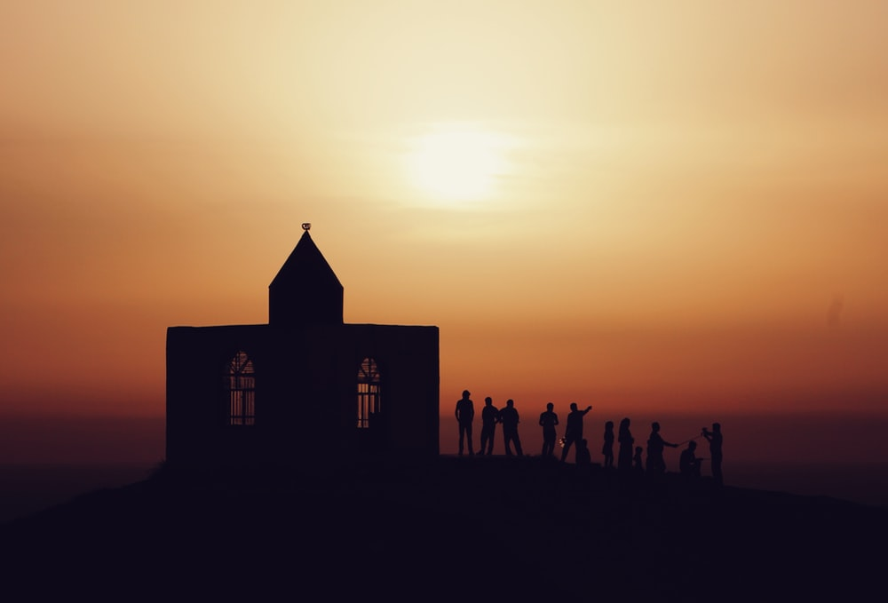 silhouette of people standing near church during sunset