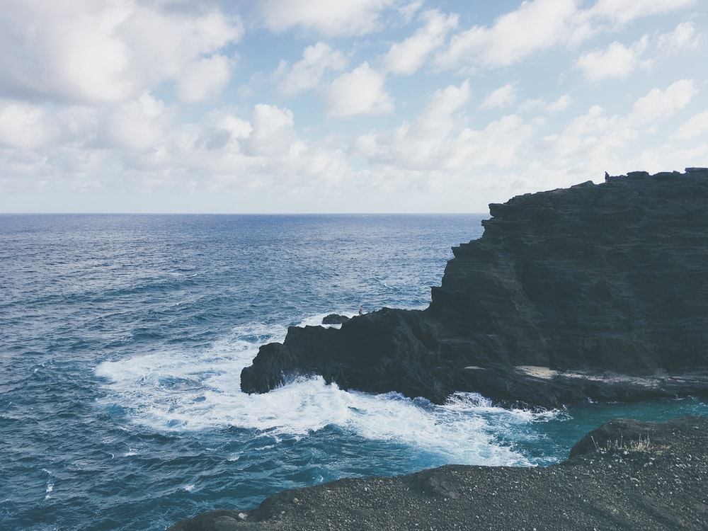ocean waves crashing on black rock formation under white clouds and blue sky during daytime