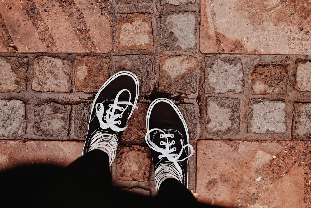 person in black and white sneakers standing on brown brick floor