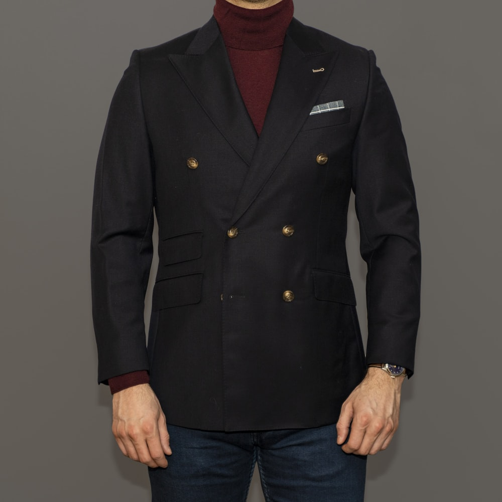 man in black coat and blue denim jeans