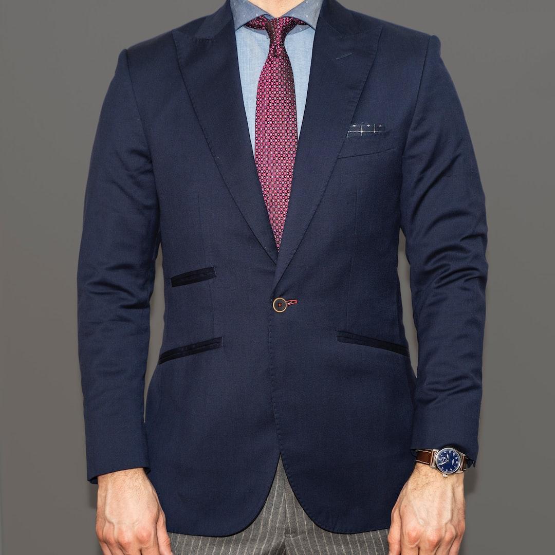Dapper Professional wearing a custom blue blazer, bold pinstripe slacks and a red tie.