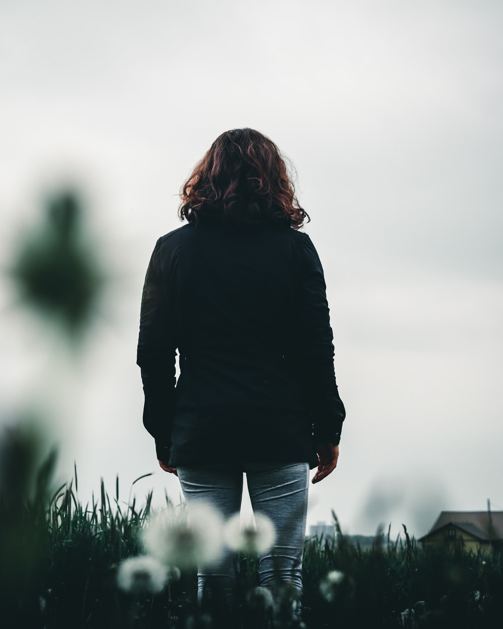 woman in black jacket standing on green grass field during daytime