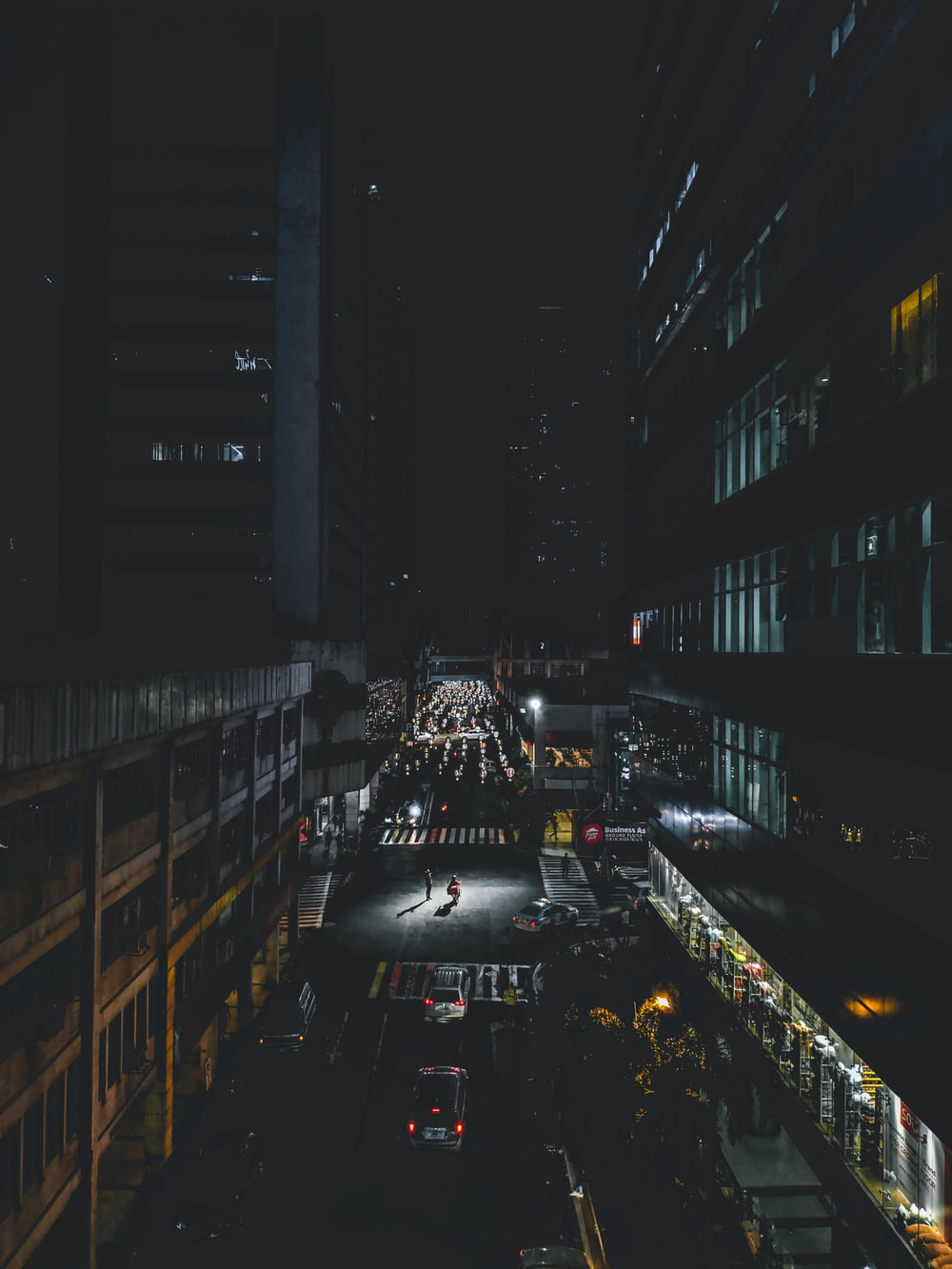 cars on road in between high rise buildings during night time
