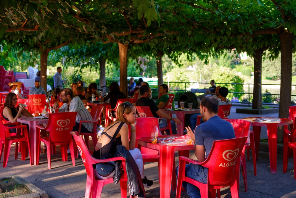 people sitting on red plastic chairs during daytime