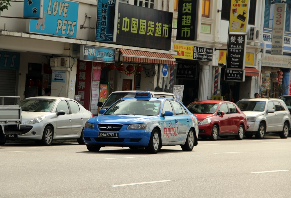 blue and white sedan on road near store during daytime