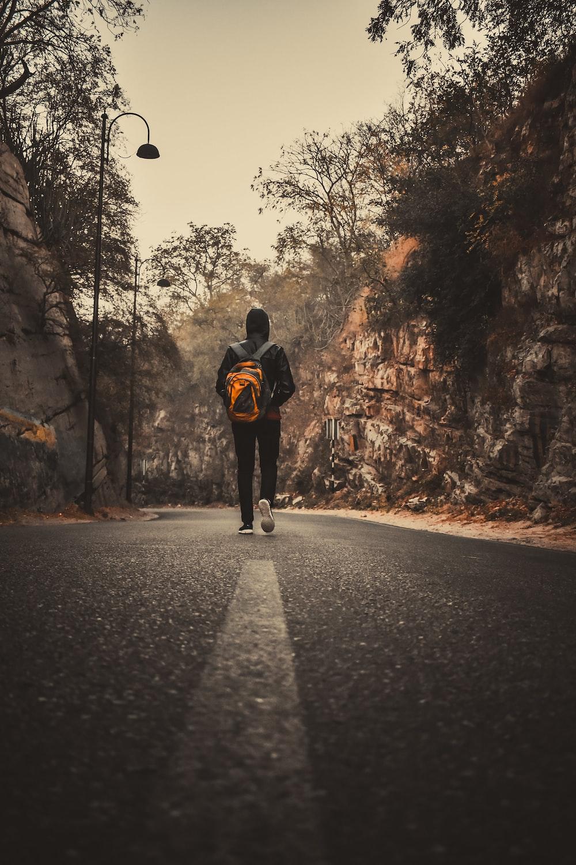 man in black jacket and black pants walking on road during daytime