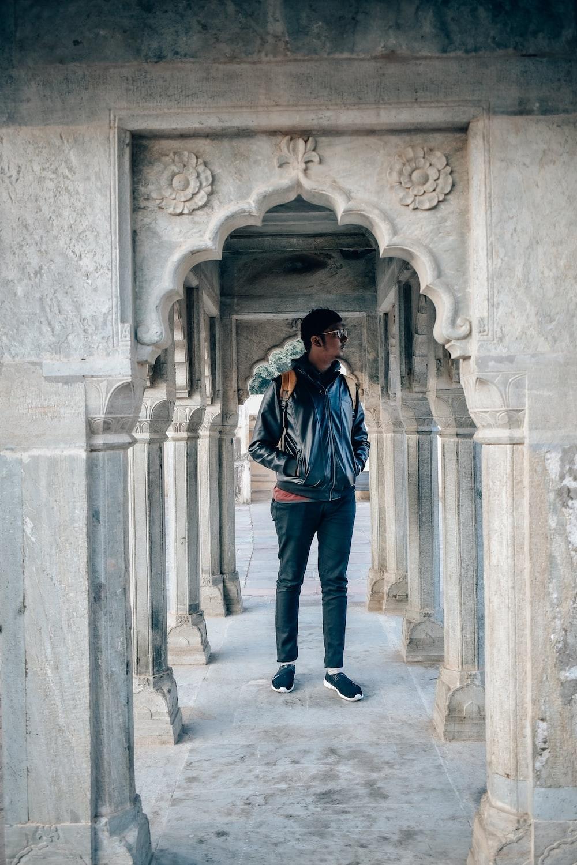 man in blue jacket standing on hallway