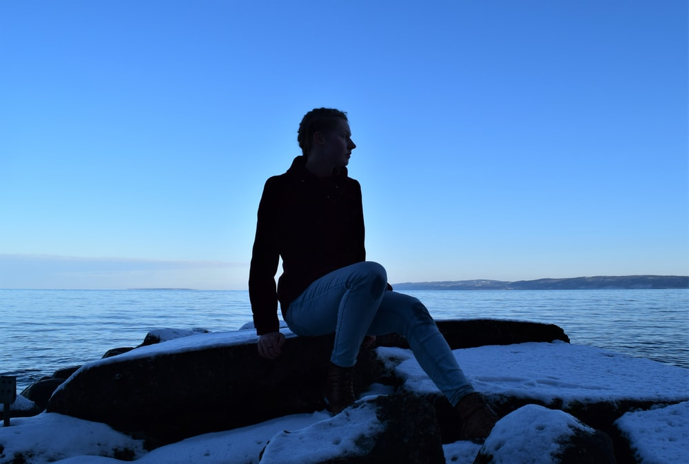 man in black jacket and blue denim jeans sitting on rock near sea during daytime