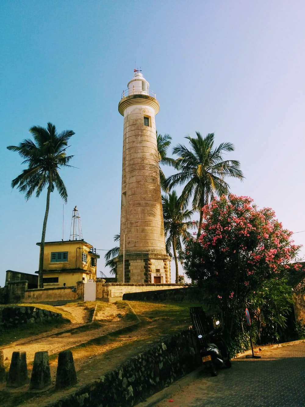 white and brown lighthouse near green trees during daytime