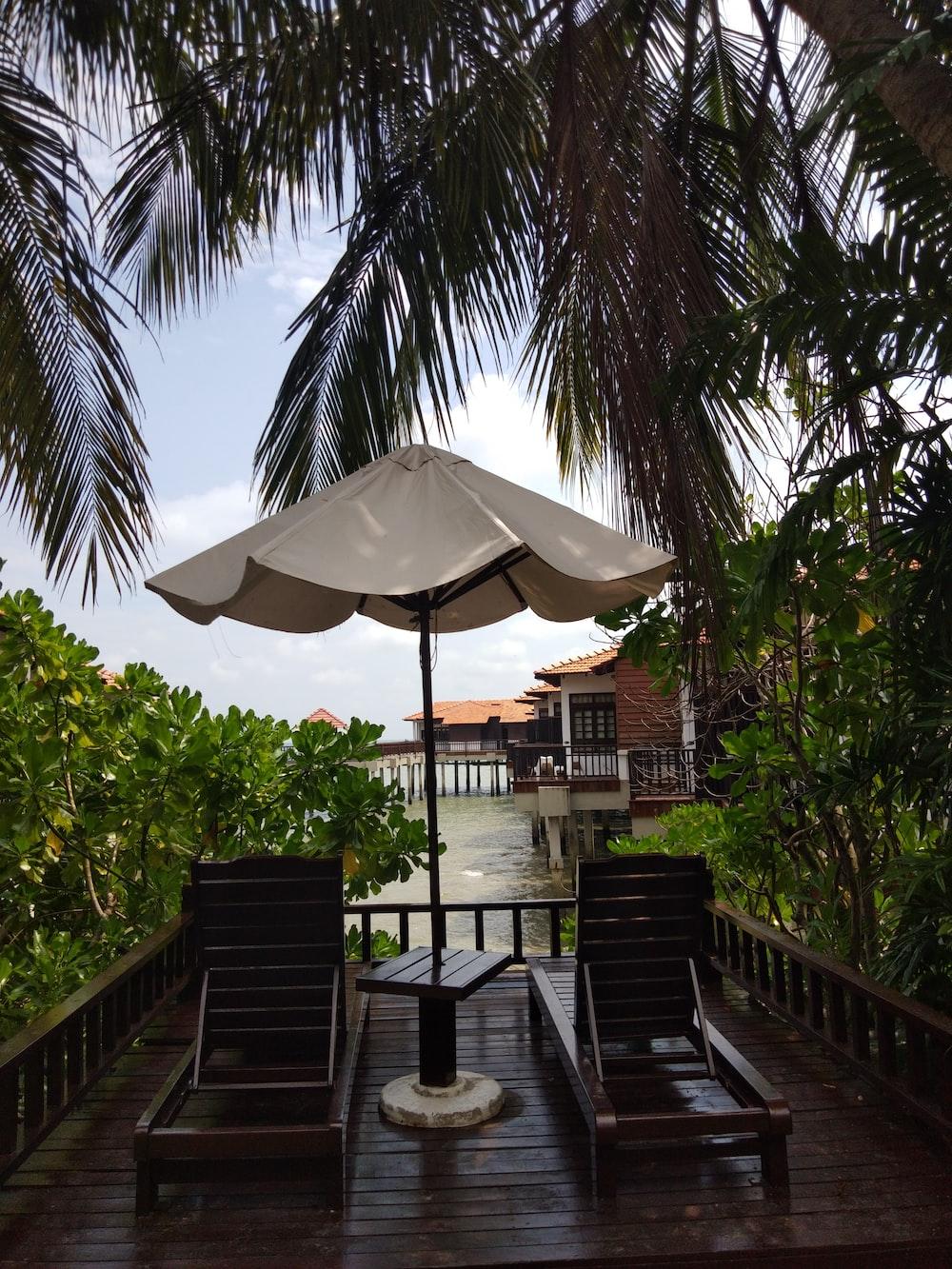 white patio umbrella near green palm trees during daytime