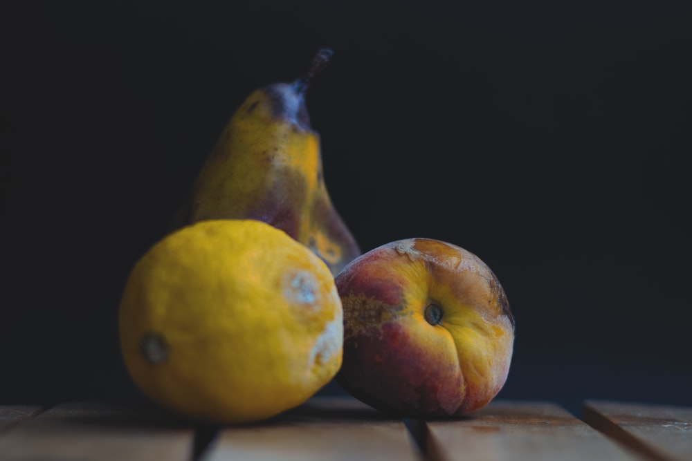 two yellow and red apples on brown wooden table