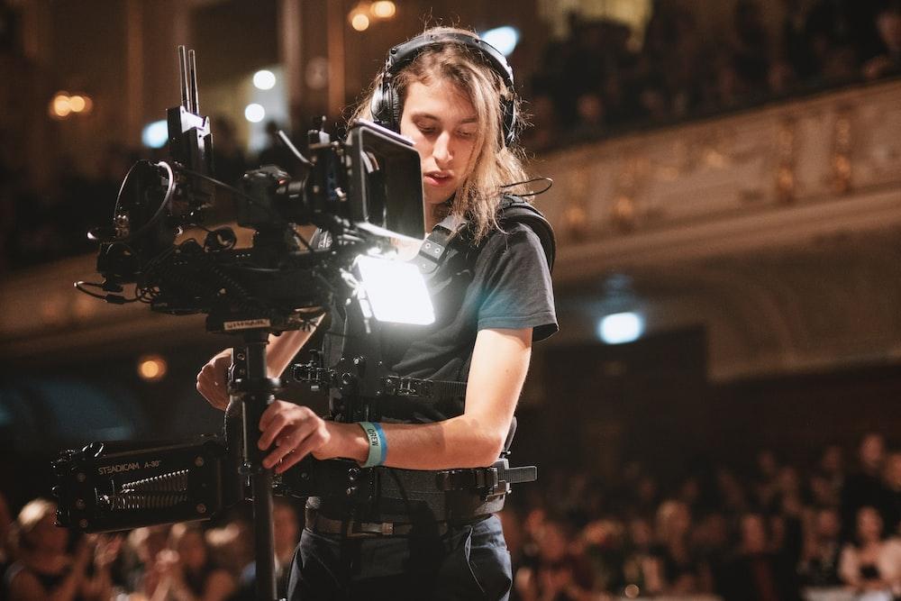 woman in black t-shirt holding black video camera
