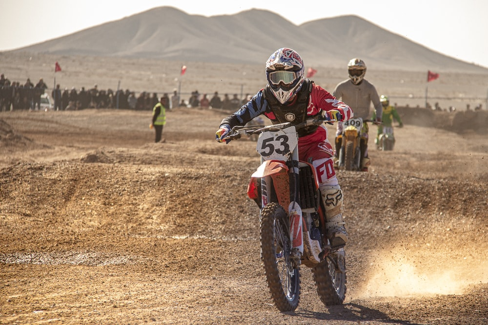 man in red and white motocross suit riding motocross dirt bike