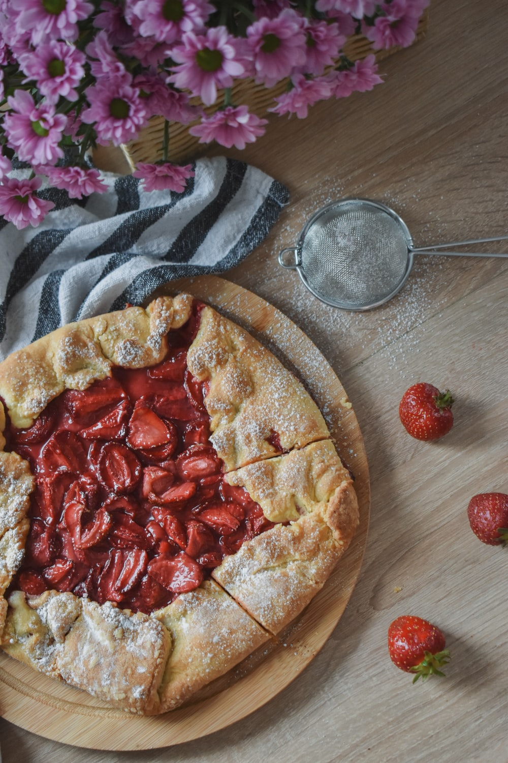 pizza with red and white sliced strawberries on brown wooden round tray