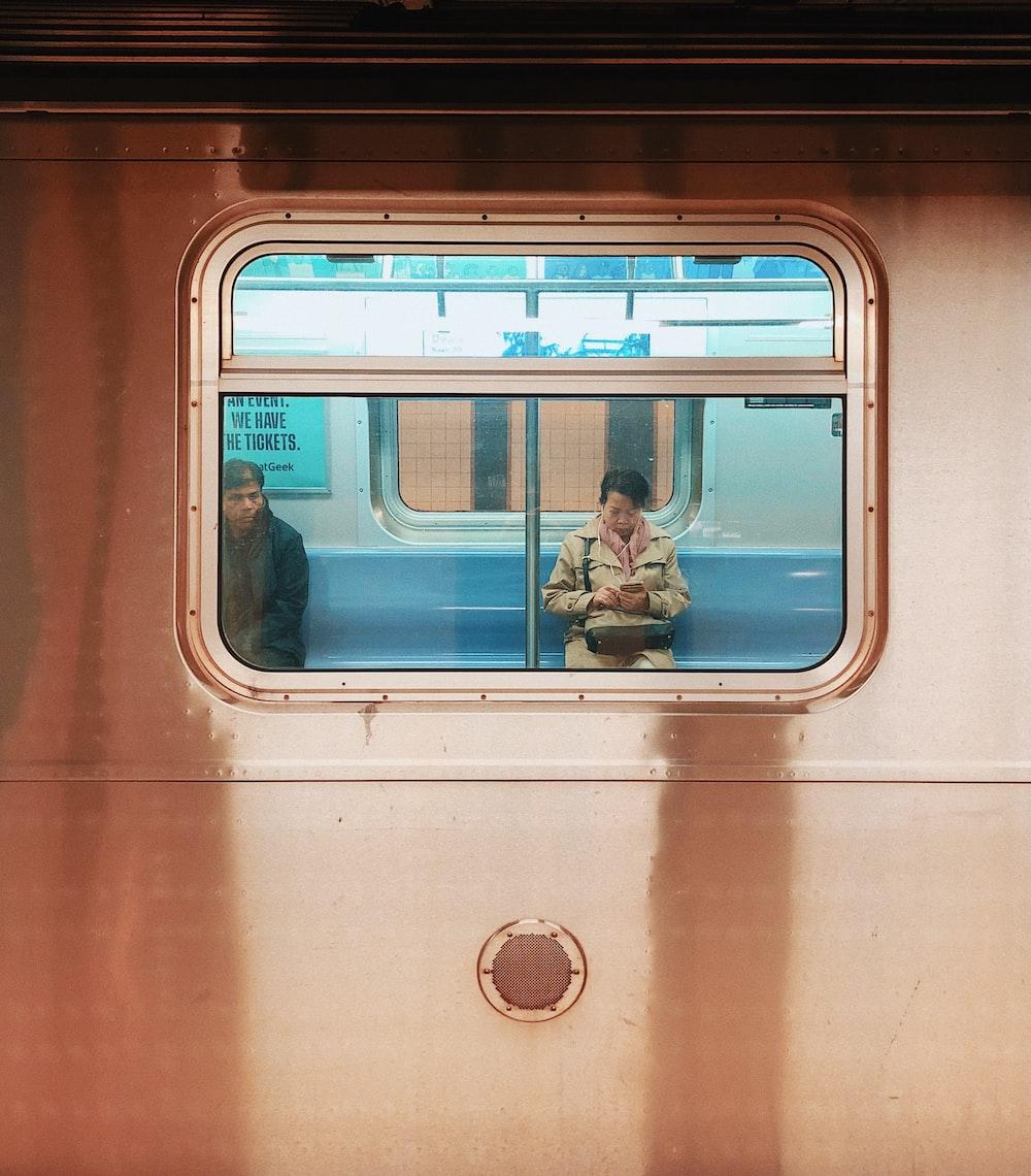 man in blue denim jeans sitting on train