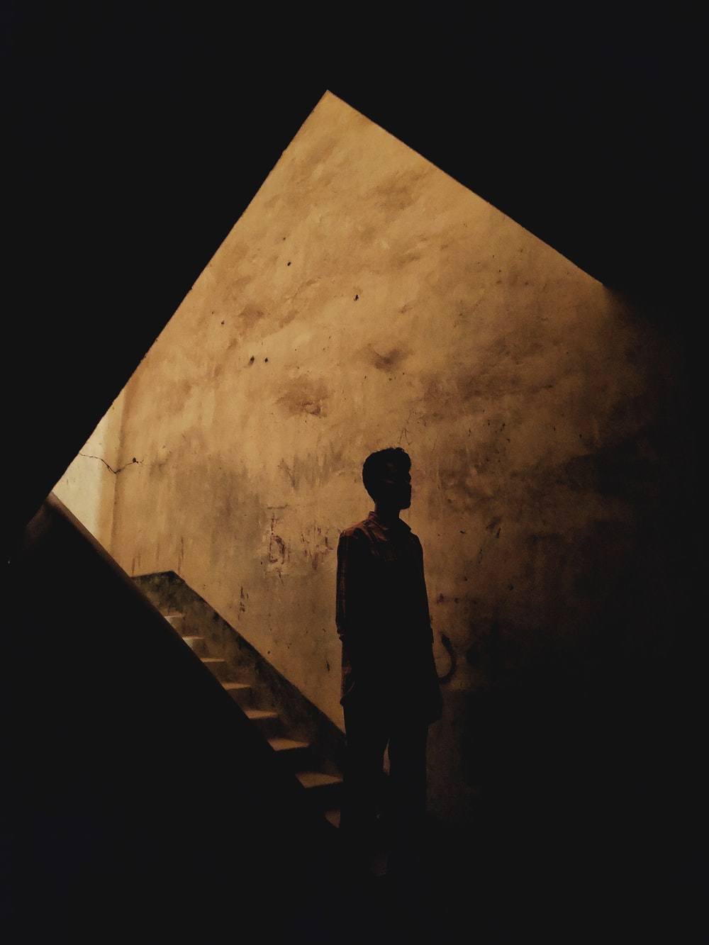 silhouette of man standing on stairs