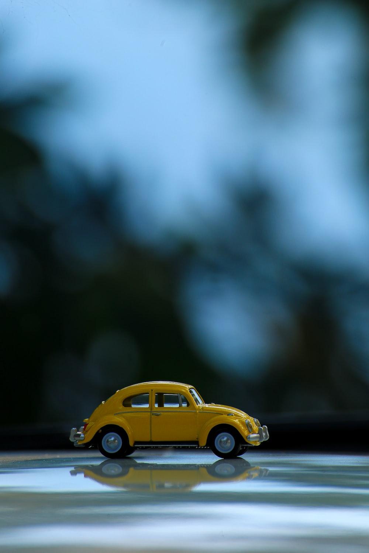 yellow volkswagen beetle on black asphalt road in tilt shift lens