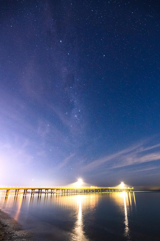 brown wooden dock under starry night