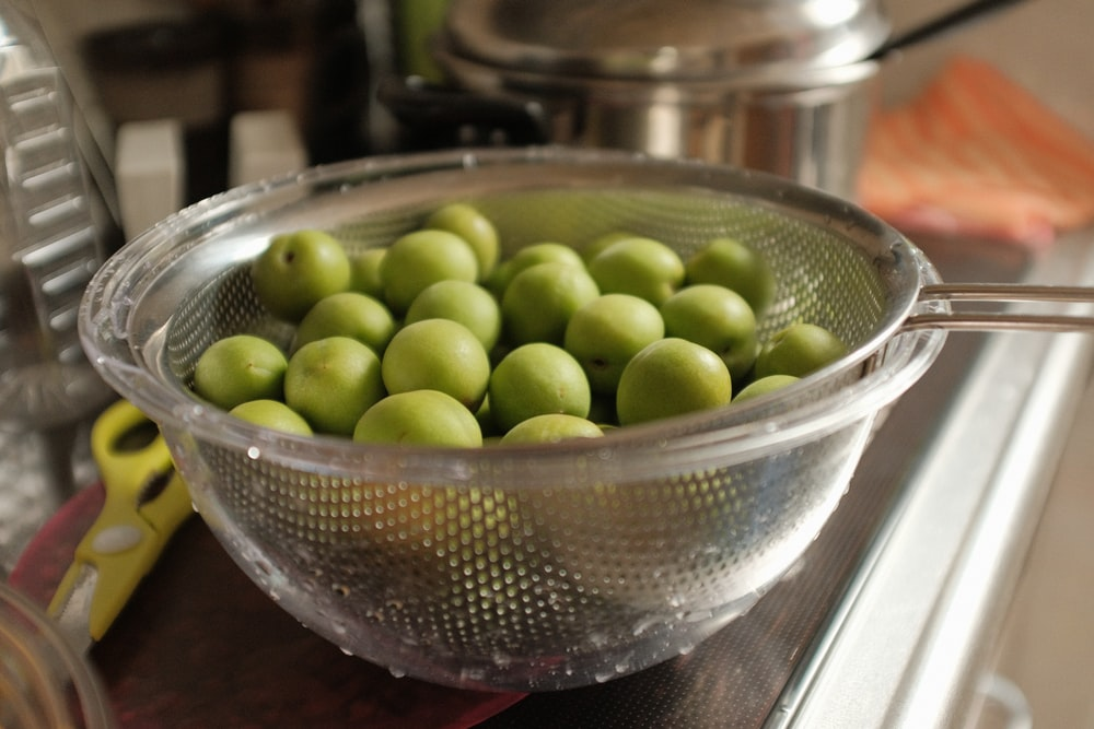 green round fruits in stainless steel bowl