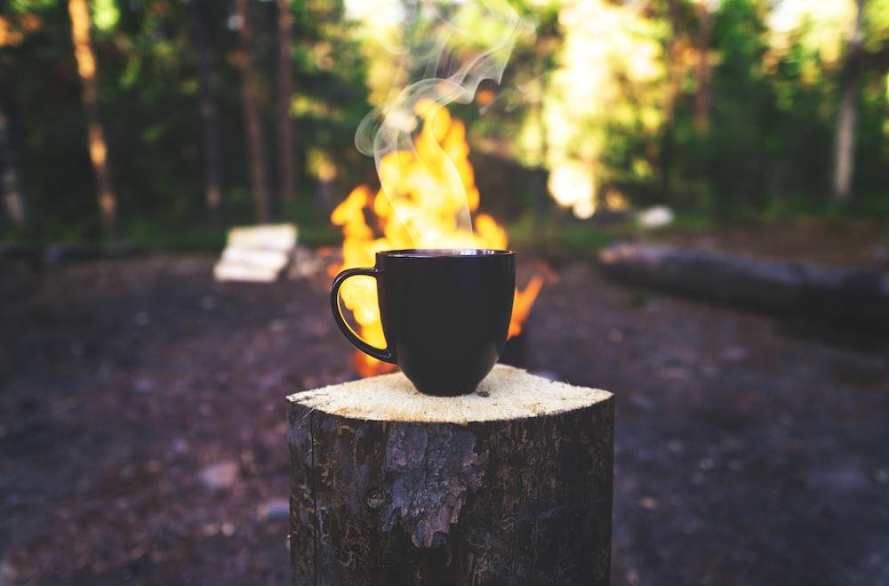 black ceramic mug on brown wooden log