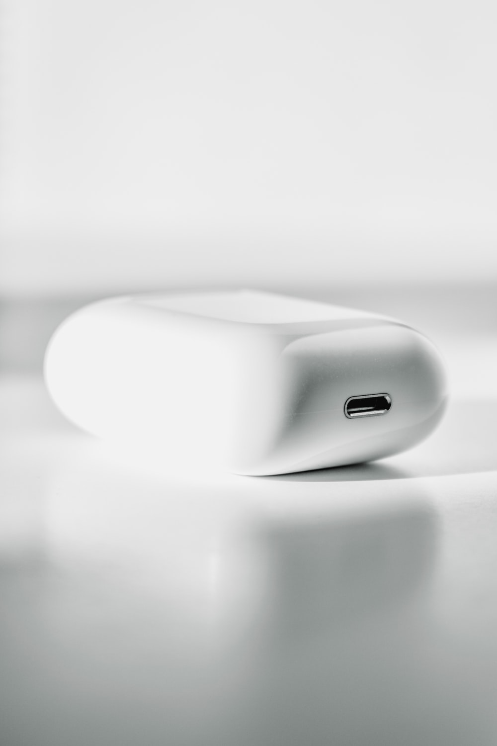 white apple charging case on white textile