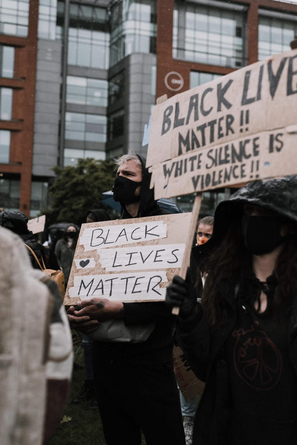 woman in black jacket holding white and black signage