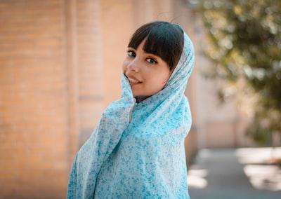 girl in blue hoodie standing iranian teams background
