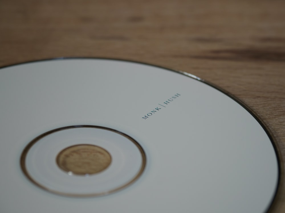 white compact disc on brown wooden table
