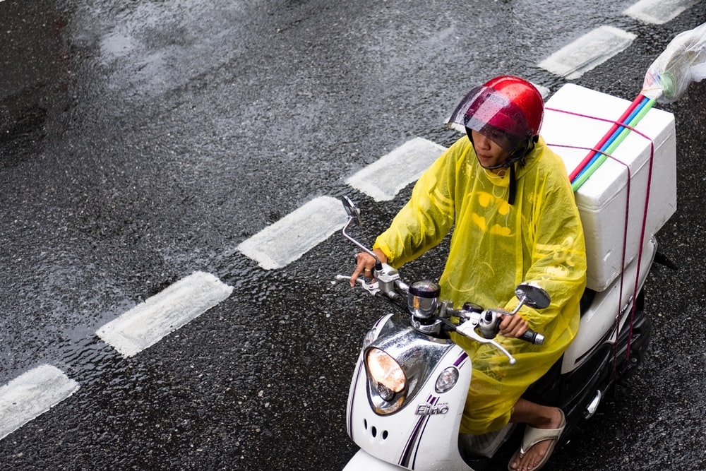 man in yellow jacket riding white motor scooter