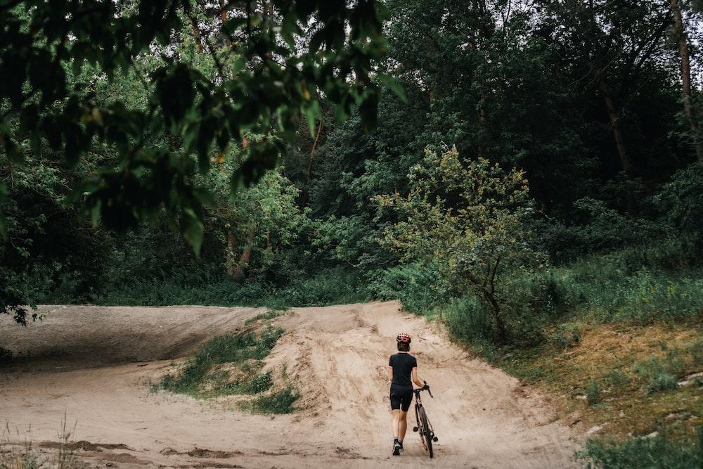 man in black shirt riding bicycle on dirt road during daytime