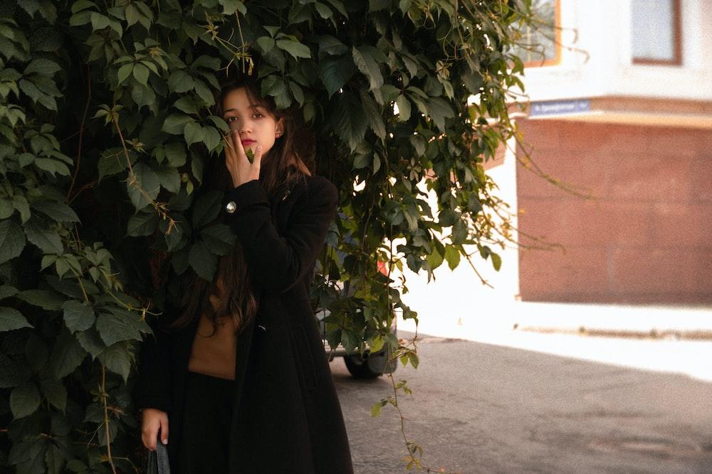 woman in black long sleeve dress standing beside green plant