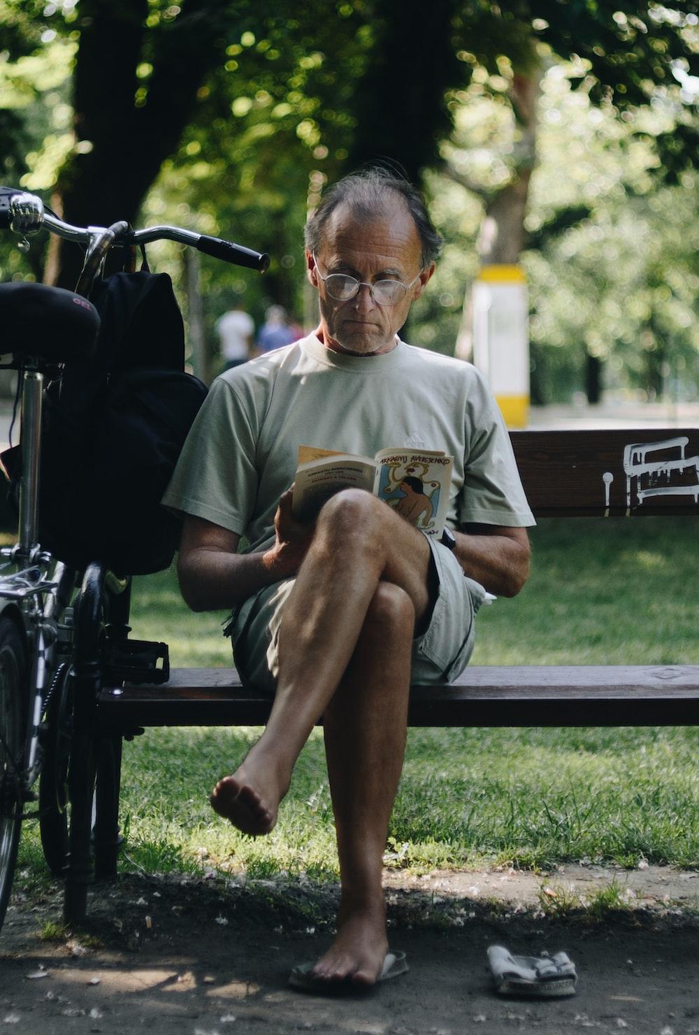 man in brown crew neck t-shirt sitting on black wooden bench during daytime