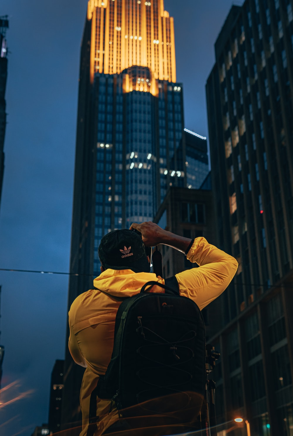 man in yellow hoodie and black backpack standing on top of building during daytime