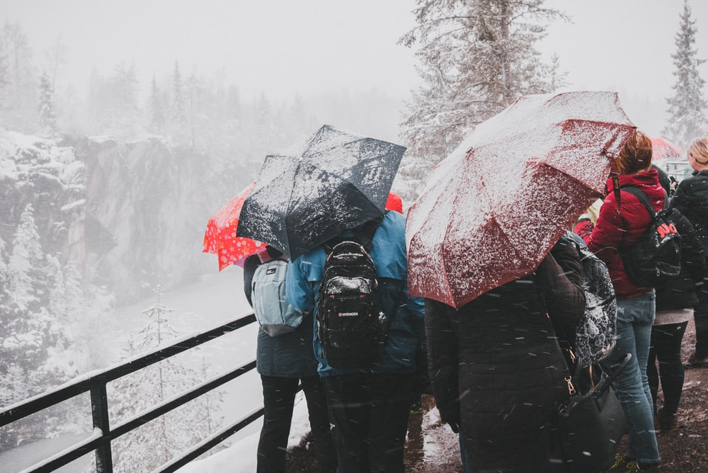 person in blue jacket and blue denim jeans holding red umbrella walking on snow covered pathway