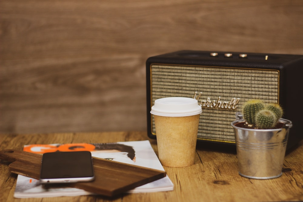 white and brown coffee cup on brown wooden table