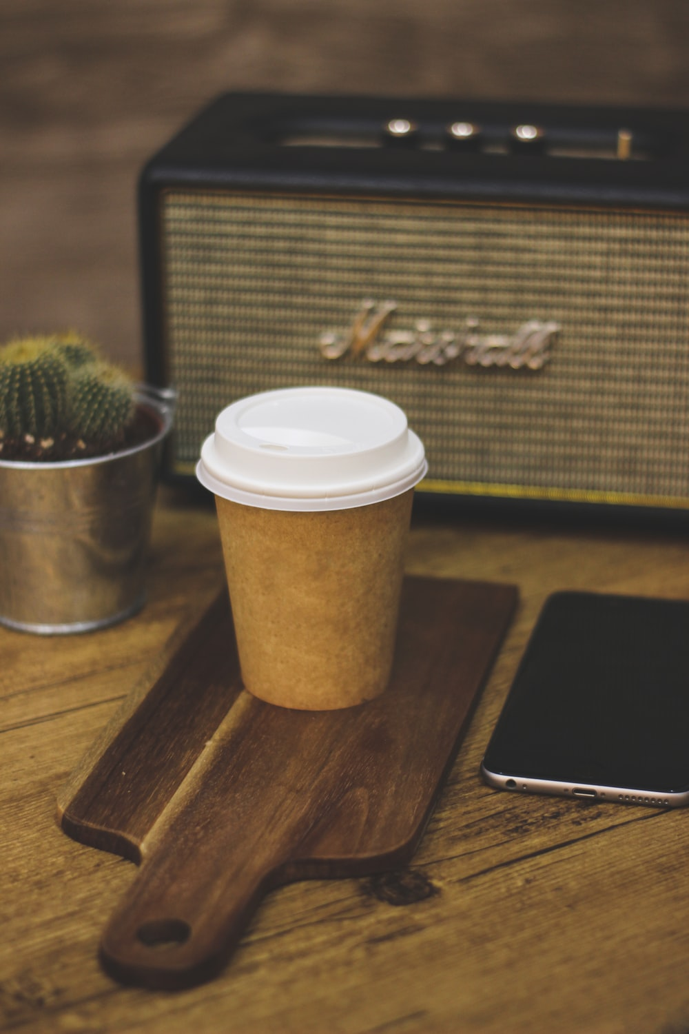 white and brown coffee cup beside silver iphone 6 on brown wooden table