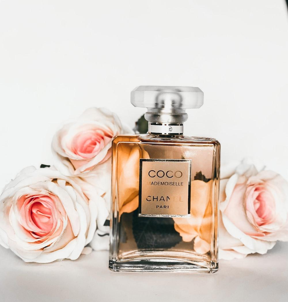 gold perfume bottle beside pink rose