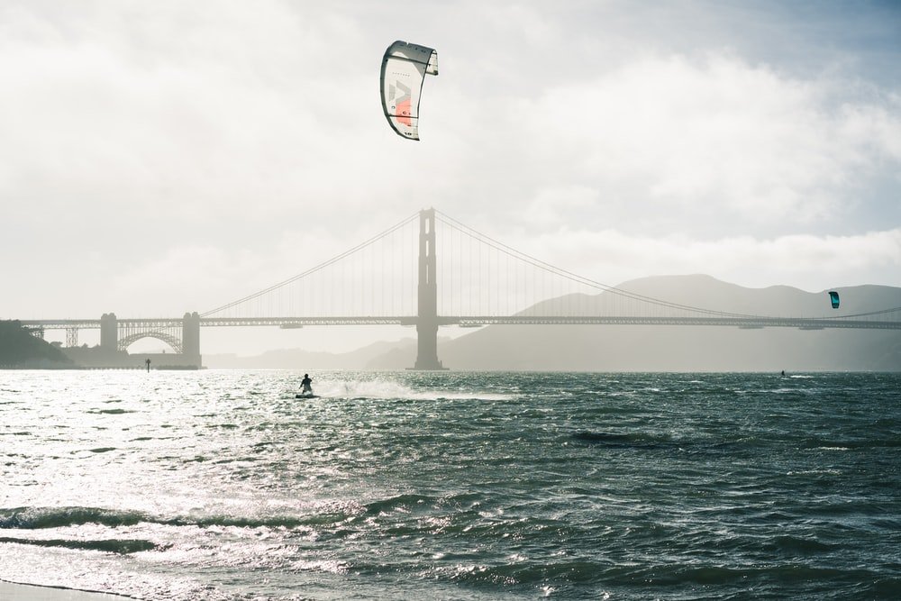 person surfing on sea near bridge under cloudy sky during daytime