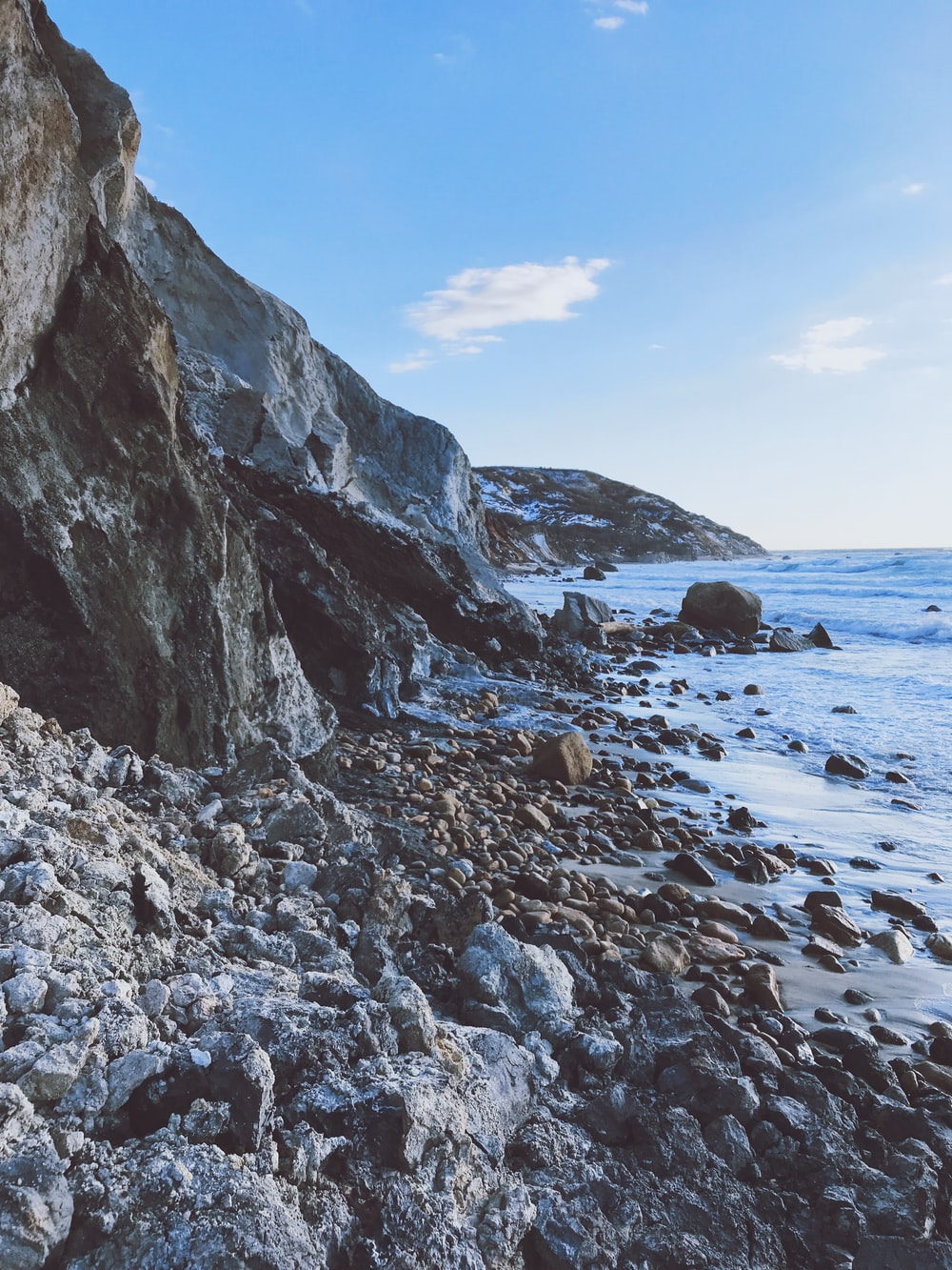 rocky shore with rocks under blue sky during daytime