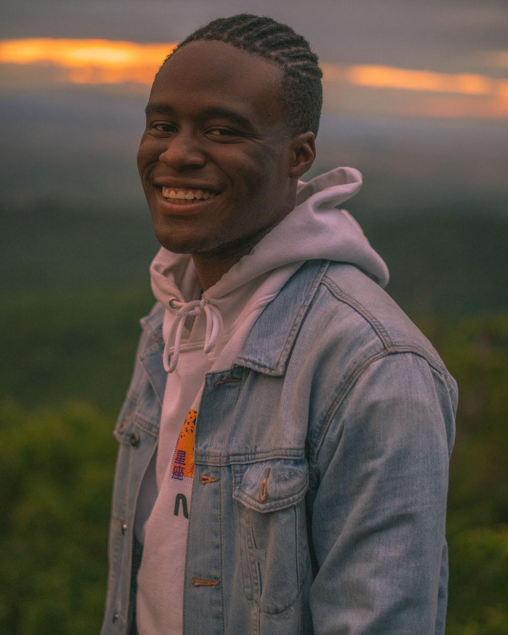 smiling man in gray denim jacket