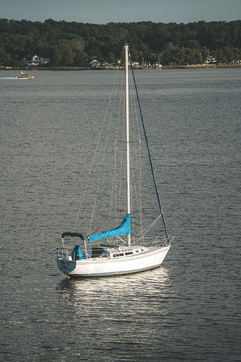 white and blue sailboat on sea during daytime